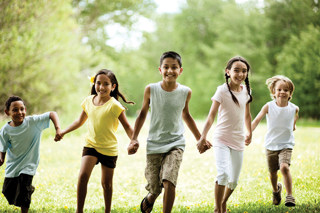 children of various ages running together holding hands